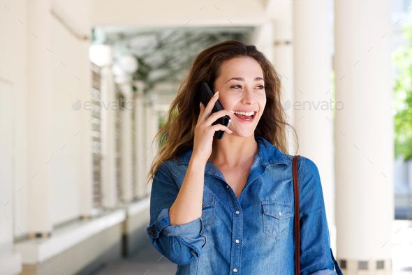happy young woman talking on mobile phone outside - Stock Photo - Images
