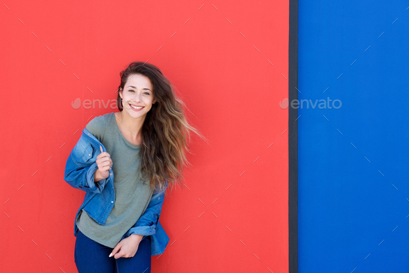 beautiful young woman laughing against red background - Stock Photo - Images