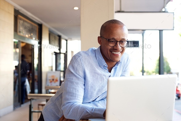 handsome african businessman working with laptop - Stock Photo - Images