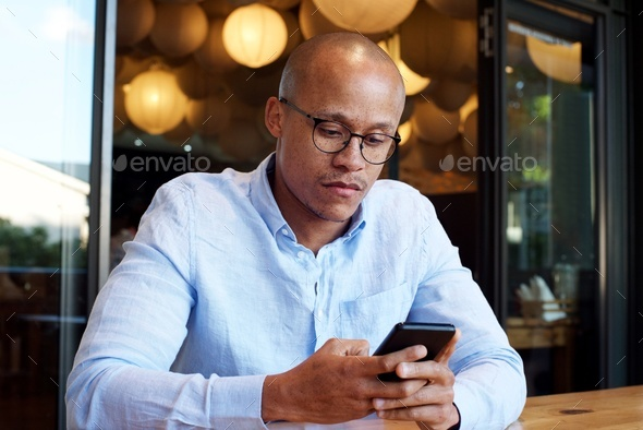 african businessman sitting with cellphone - Stock Photo - Images