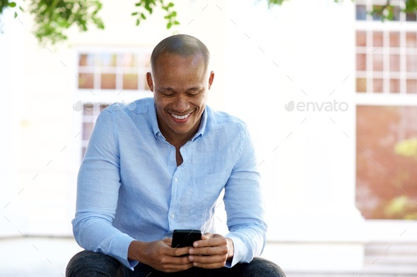cool african guy sitting outside with cellphone - Stock Photo - Images