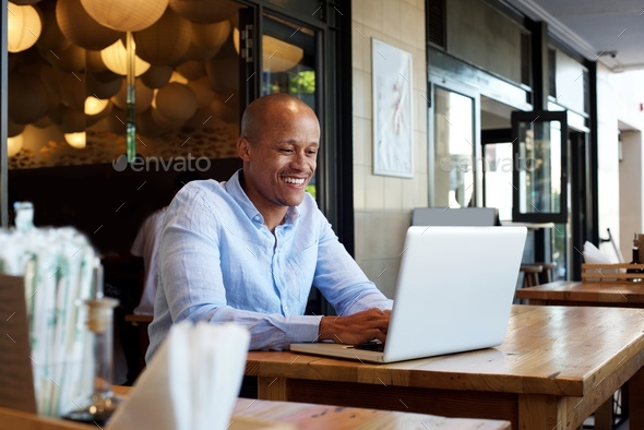 smiling businessman sitting at table with laptop - Stock Photo - Images