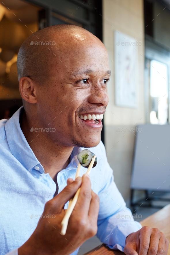 smiling african man enjoying eating sushi - Stock Photo - Images