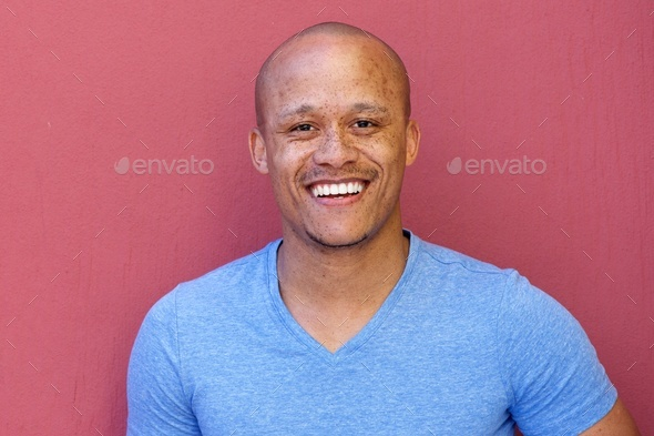 handsome african american man smiling against red background - Stock Photo - Images