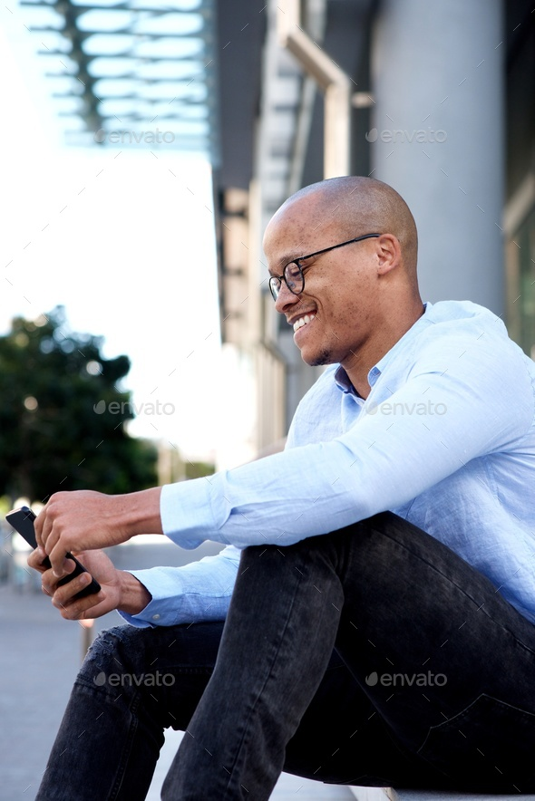 african businessman sitting outside with mobile phone - Stock Photo - Images