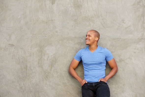 handsome black man in t-shirt smiling and looking away - Stock Photo - Images