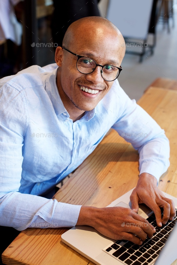 black businessman sitting with laptop - Stock Photo - Images