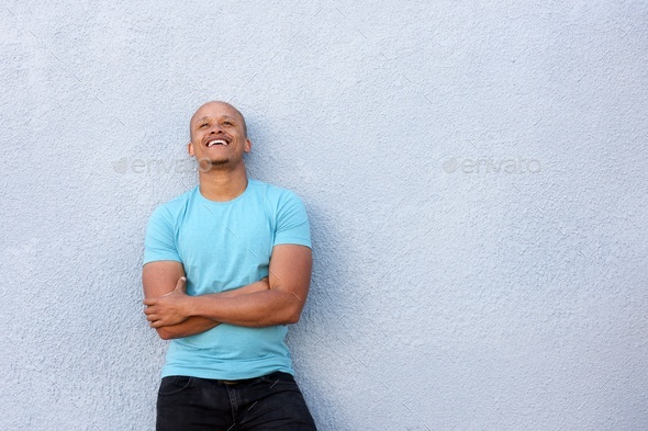african american guy laughing with arms crossed looking up - Stock Photo - Images