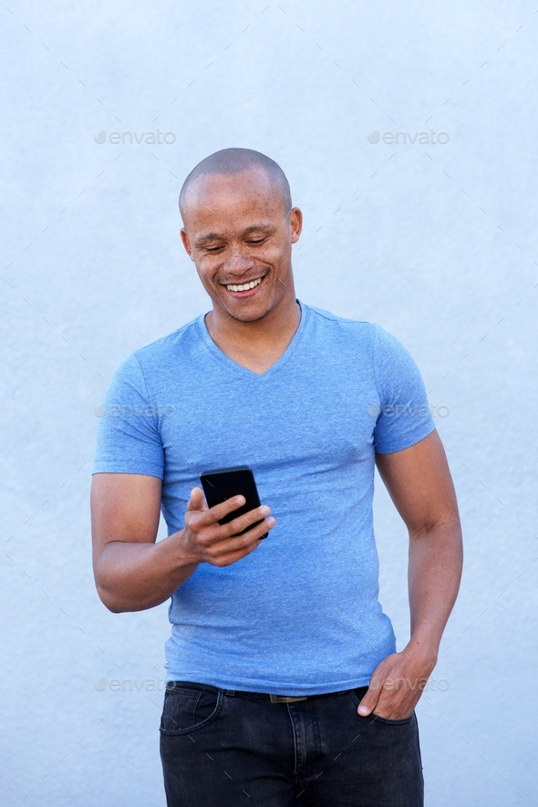 cool african guy smiling with cellphone - Stock Photo - Images