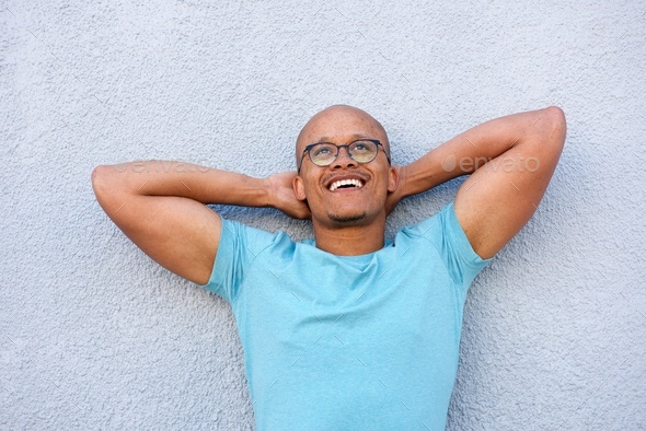african american man smiling with glasses looking up in contemplation - Stock Photo - Images