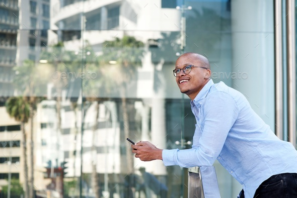 african businessman standing outside with cellphone - Stock Photo - Images