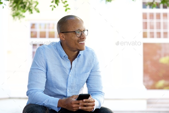 african american businessman sitting outside with mobile phone - Stock Photo - Images