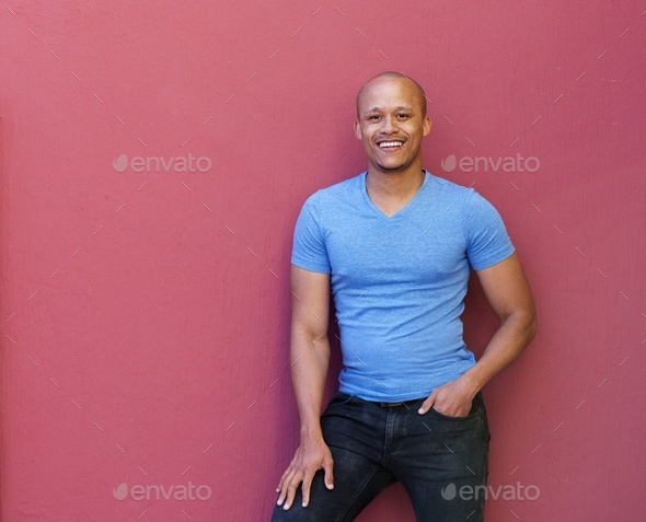 handsome cool african man smiling against red background - Stock Photo - Images