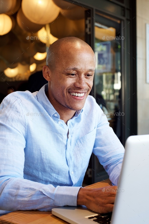 smiling african businessman working on laptop - Stock Photo - Images