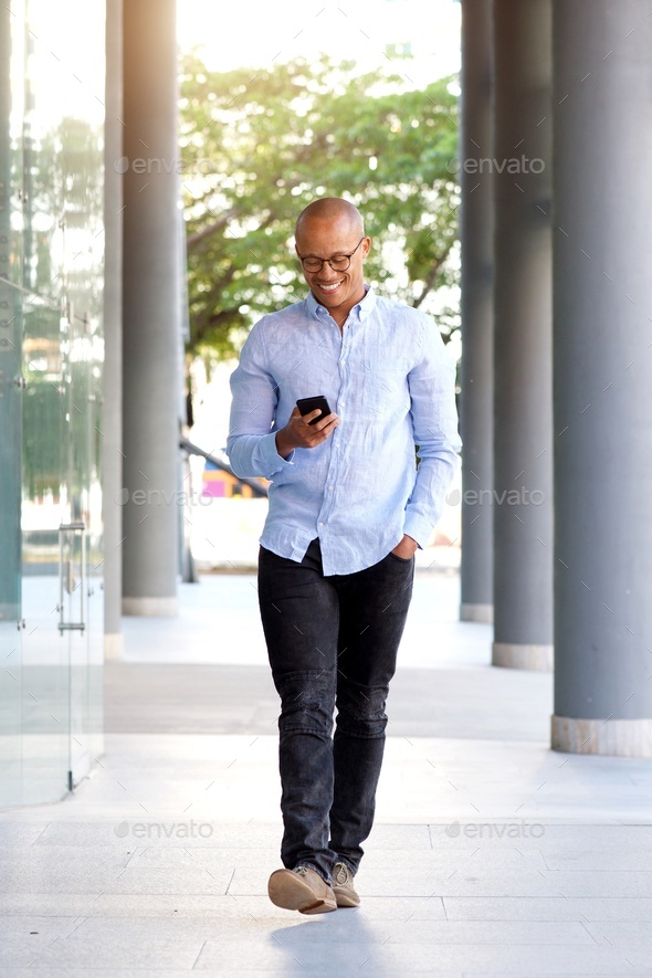 smiling african guy walking with mobile phone - Stock Photo - Images