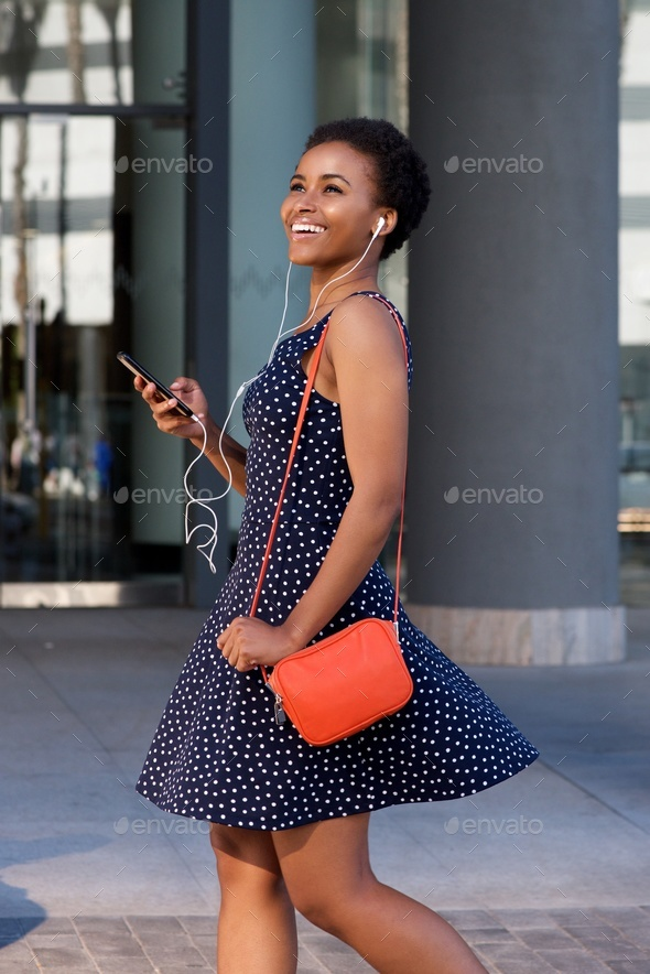 smiling black woman walking and listening to music on earphones - Stock Photo - Images