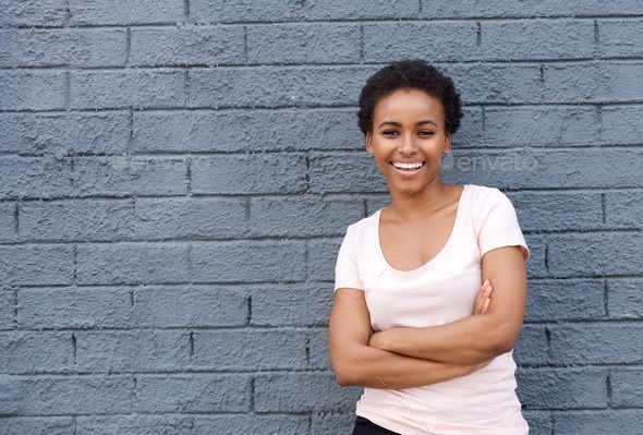 beautiful young african american woman smiling against gray wall - Stock Photo - Images