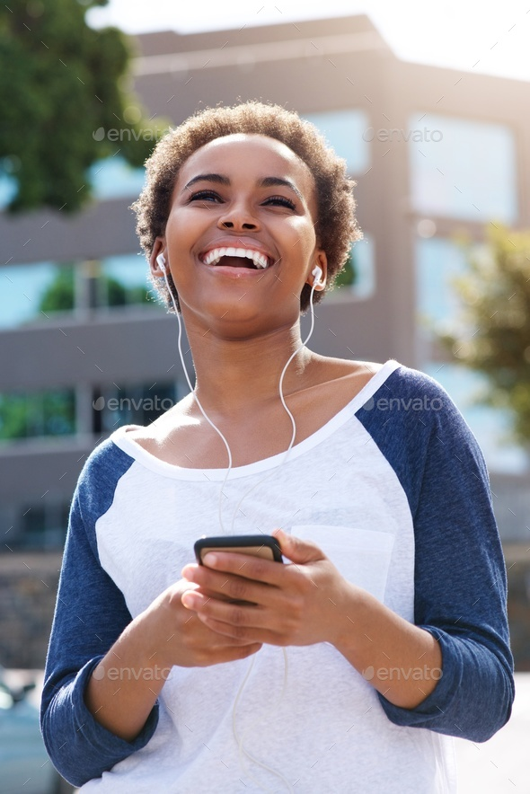 beautiful young black woman laughing with earphones and cellphone - Stock Photo - Images