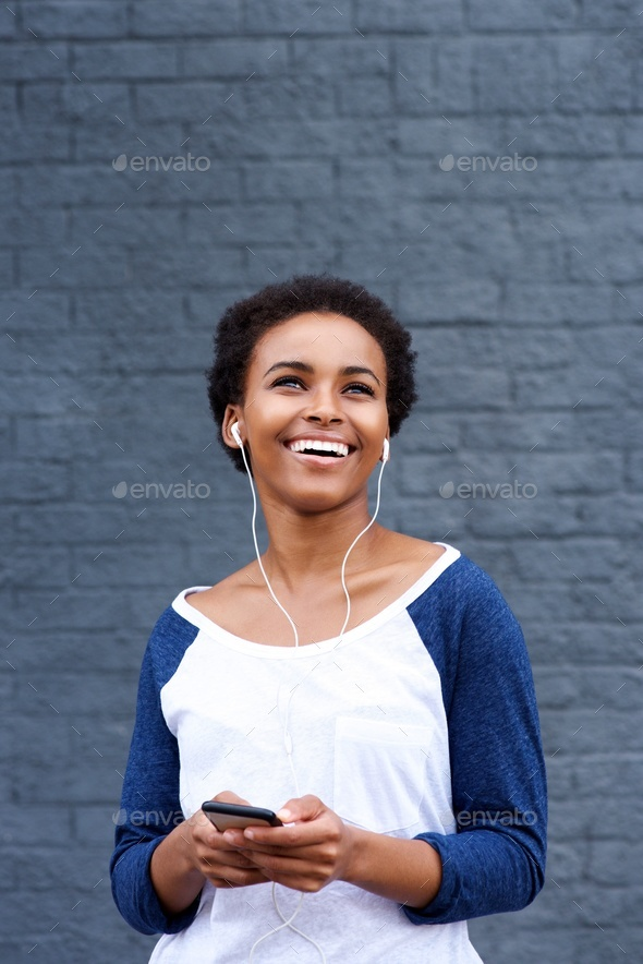 Young smiling woman listening to music with earphones and cell phone - Stock Photo - Images