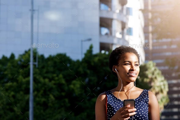 beautiful black woman smiling with earphones and cellphone in city - Stock Photo - Images
