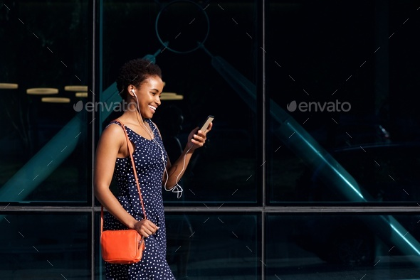 smiling young african woman walking with phone and earphones - Stock Photo - Images