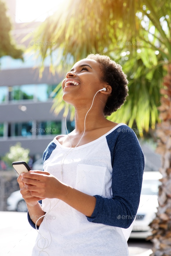 happy young black woman listening to music on cellphone - Stock Photo - Images