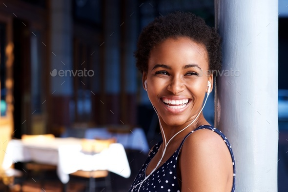 attractive young black woman laughing with earphones - Stock Photo - Images