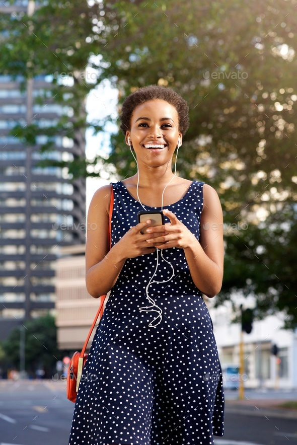 attractive young black woman walking in city with mobile and earphones - Stock Photo - Images
