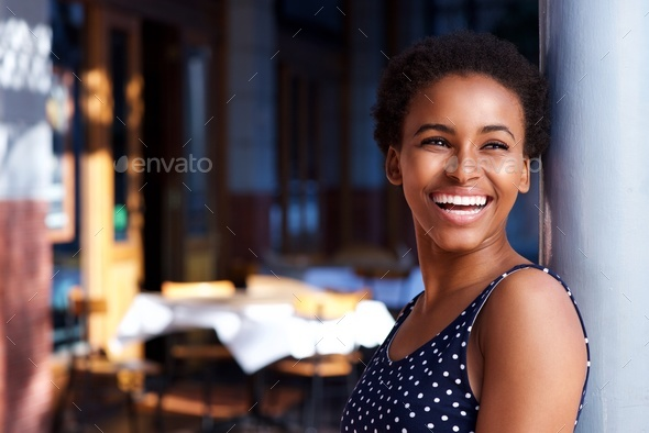 smiling young black woman standing outside - Stock Photo - Images