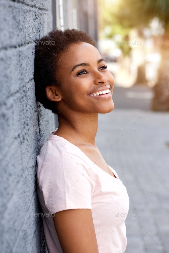 smiling young african woman smiling outside - Stock Photo - Images