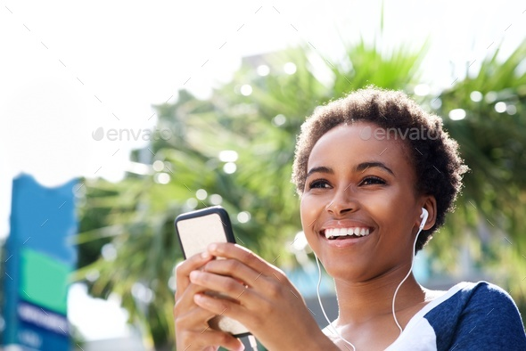smiling young african woman listening to music with earphones - Stock Photo - Images