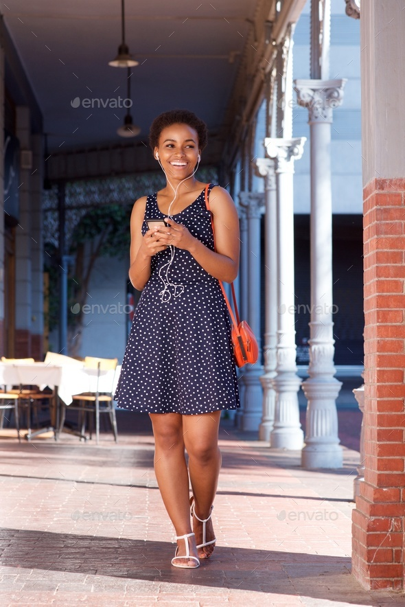 smiling young black woman walking with cellphone and earphones - Stock Photo - Images