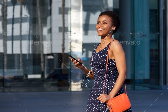 smiling young black woman walking with earphones and mobile phone - Stock Photo - Images