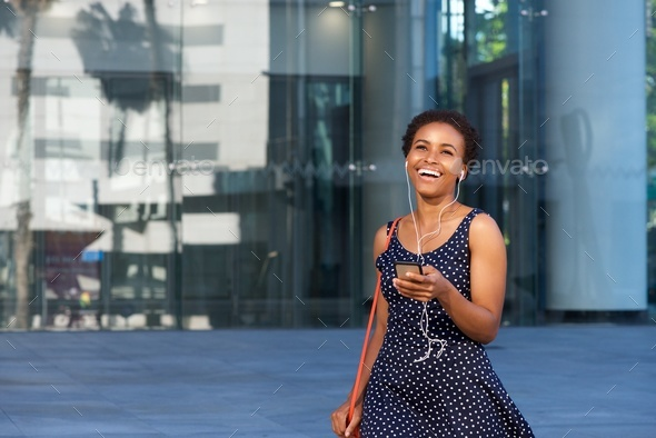 young african woman walking in city with mobile phone and earphones - Stock Photo - Images