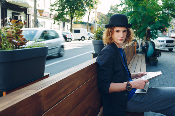 Red haired hipster man sitting on bench with newspaper - Stock Photo - Images