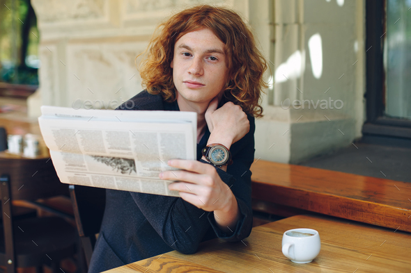 Young man reading a newspaper in the morning - Stock Photo - Images