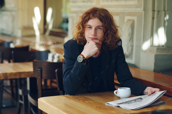 Young man thinking while having coffee - Stock Photo - Images