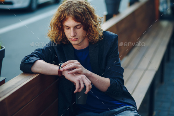 Man looking to the watch on his hand - Stock Photo - Images