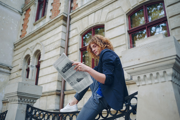 Young reddish man reading newspaper near old style building - Stock Photo - Images