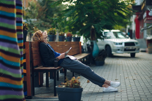 Man dreaming while lying on a long wooden bench - Stock Photo - Images