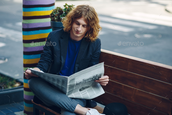 Red haired hipster man sitting on bench reading newspaper - Stock Photo - Images