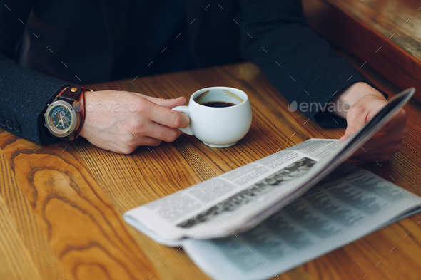 Man's hands close-up holding cup of coffee and a newspaper - Stock Photo - Images