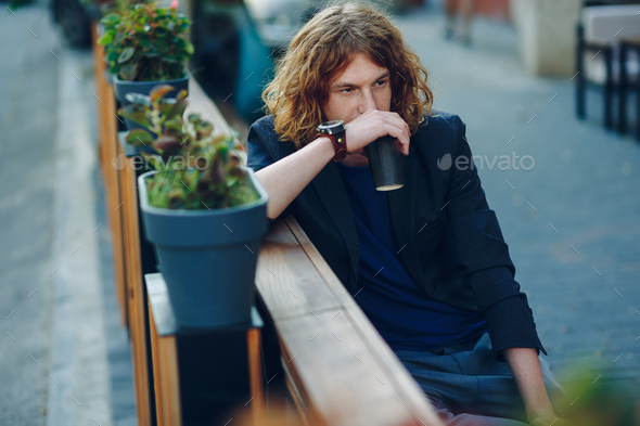 Man resting on a bench with a coffee to go - Stock Photo - Images