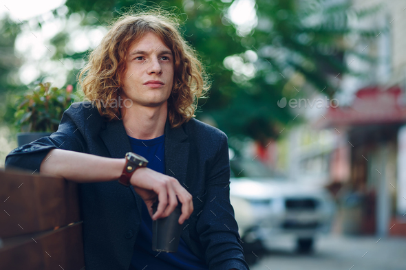Man sitting on bench thinking - Stock Photo - Images