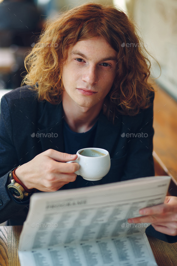 Hipster man drinking coffee while reading - Stock Photo - Images