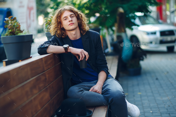 Red haired hipster man sitting on bench with coffe to go - Stock Photo - Images