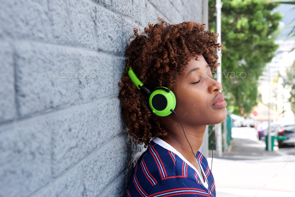 african woman listening to music with headphones - Stock Photo - Images