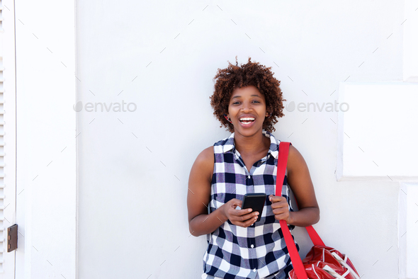 african woman laughing with mobile phone and bag outside - Stock Photo - Images