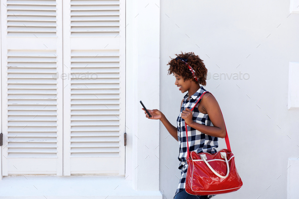 smiling african woman walking with cellphone and bag - Stock Photo - Images