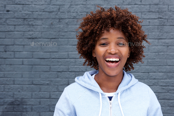 african woman laughing against gray brick wall - Stock Photo - Images